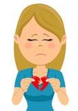 Junge unglückliche traurige Frau mit einer Karte des defekten Herzens Lizenzfreies Stockfoto