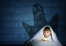 Junge unter den Abdeckungen mit einer Taschenlampe Stockfotos