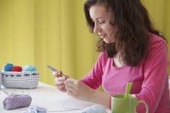 Junge unternehmungslustige Frau, die handgemachte Knitkleidung herstellt Stockfotografie