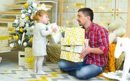 Junge Vater- und Kleinkindtochter, die zu Hause Geschenkboxen nahe verziertem Weihnachtsbaum hält lizenzfreie stockfotos