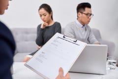 Junge verärgerte Paare von den betrogenen Investoren, welche die Papiere argumentieren mit männlicher Immobilienagentur, betrogen lizenzfreies stockbild