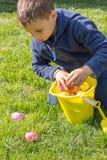 Junge verbiegt über seinen Eimer, um Ostern zu sammeln  Stockfotos