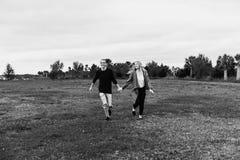 Junge verbinden in der Liebe, die im Frühjahr in ein großes offenes Feld-Händchenhalten im Freien und das Lachen läuft stockfotos