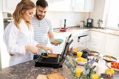 Junge verbinden die Herstellung von Toast in der Küche stockbilder