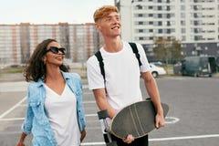 Junge verbinden mit dem Skateboard, das Spaß an der Stadt-Straße hat lizenzfreie stockbilder