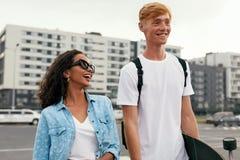 Junge verbinden mit dem Skateboard, das Spaß an der Stadt-Straße hat stockbilder