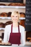 Junge Verkäuferin, die in der Bäckerei arbeitet Stockbilder