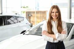 Junge Verkäuferin, die nahen Neuwagen steht lizenzfreie stockfotos
