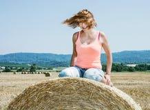 Junge verrückte kaukasische Frau sitzt auf dem Stapel des Strohs und des Wurfs Stockfoto