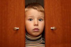 Junge versteckt sich in der Garderobe Stockbild
