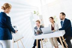 Junge vier Kollegen, die bei der Sitzung sich darstellen Lizenzfreies Stockfoto