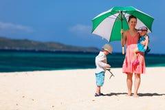 Junge vierköpfige Familie auf tropischem Strand des weißen Sandes Stockfotos