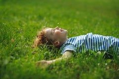 Junge von 8-9 Jahren liegt auf dem Gebiet auf einem grünen Gras Stockfoto
