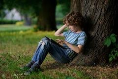 Junge von 8-9 Jahren mit Begeisterung wird auf der Tablette engagiert Stockfotografie