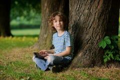 Junge von 8-9 Jahren sitzt das Lehnen gegen einen Baum und hält die Tablette in der Hand Stockfotos