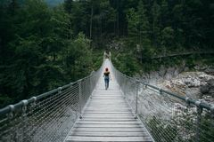 Junge Wandererfrau geht auf Hängebrücke lizenzfreies stockbild