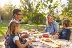 Junge weiße Familie, die ein Picknick an einem Tisch in einem Park genießt Stockfotos