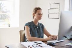 Junge weiße Frau, die oben im Büro unter Verwendung des Computers, Abschluss arbeitet lizenzfreies stockbild