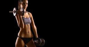 Junge weiße Frau hebt Gewichte auf einem schwarzen Hintergrund mit Kopienraum an Stockfotografie