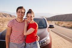 Junge weiße Paarstellung auf Wüstenstraßenrand mit dem Auto lizenzfreies stockbild