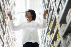 Junge weibliche Chemiker-Arranging Stock In-Regale an der Apotheke lizenzfreies stockbild