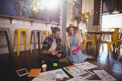 Junge weibliche darstellende Berufsmolkerei zum männlichen Kollegen an der Kaffeestube lizenzfreies stockfoto
