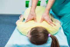 Junge weibliche empfangende Massage vom Chiropraktor des Therapeuten A, der seinen geduldigen ` s Dorn im Ärztlichen Dienst ausde Stockfoto