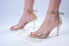 Junge weibliche Füße in den goldenen hohen Absätzen und in der Perlenhalskette auf weißem Hintergrund lizenzfreie stockfotografie
