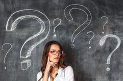 Junge weibliche Geschäftsfrau in den Gläsern arrounded Fragezeichen Stockfotos