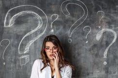 Junge weibliche Geschäftsfrau in den Gläsern arrounded Fragezeichen Lizenzfreie Stockfotos