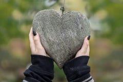 2 junge weibliche Hände mit den schwarzen Fingernägeln, die ein hölzernes Herz umfasst mit Flechte als Symbol der Freundschaft, L stockfotos