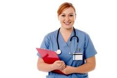 Junge weibliche Krankenschwester, die Klemmbrett hält Lizenzfreie Stockfotografie