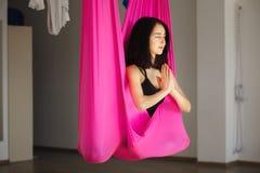 Junge weibliche Person in der rosa Hängematte, die aero Yoga tut Stockfoto