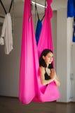 Junge weibliche Person in der rosa Hängematte, die aero Yoga tut Lizenzfreie Stockfotografie