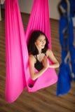 Junge weibliche Person in der rosa Hängematte, die aero Yoga tut Lizenzfreie Stockfotos