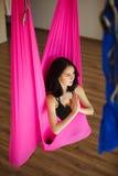 Junge weibliche Person in der rosa Hängematte, die aero Yoga tut Stockfotografie