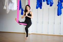Junge weibliche Person in der rosa Hängematte sitzt in Yogaposition Lizenzfreies Stockfoto