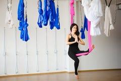 Junge weibliche Person in der rosa Hängematte sitzt in Yogaposition Lizenzfreie Stockfotografie