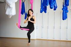 Junge weibliche Person in der rosa Hängematte sitzt in Yogaposition Lizenzfreies Stockbild
