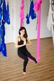 Junge weibliche Person in der rosa Hängematte sitzt in Yogaposition Stockfotografie