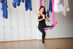 Junge weibliche Person in der rosa Hängematte sitzt in Yogaposition Stockbild