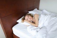Junge weibliche Person, die am Morgen auf hölzernem Bett mit weißen Leinen schläft stockfoto