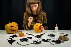 Junge weibliche Person, die Steckfassung ` O ` Laterne für Halloween schnitzt Lizenzfreies Stockfoto
