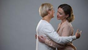 Junge weibliche umarmende ältere Mutter auf grauem Hintergrund, familiäre Beziehung, Liebe stock footage
