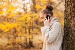 Junge weibliche Unterhaltung auf Mobiltelefon Stockbilder