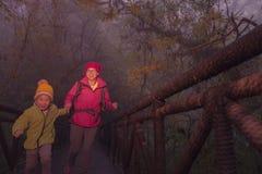Junge weibliche Wanderer- und Sohnüberfahrtbrücke im nebelhaften Wald Stockbild