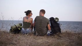 Junge, welche die Paare stillstehen auf einem Hügel wandern Wanderer der jungen Frau und des Mannes entfernen Rucksäcke, sitzend  stock footage