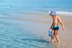 Junge, welche nach Seeoberteilen sucht stockbild