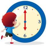 Junge, welche Zeit auf blauer Uhr sagt Lizenzfreies Stockbild