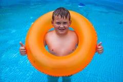 Junge, wenn Spaß im Swimmingpool gehabt wird lizenzfreie stockfotos